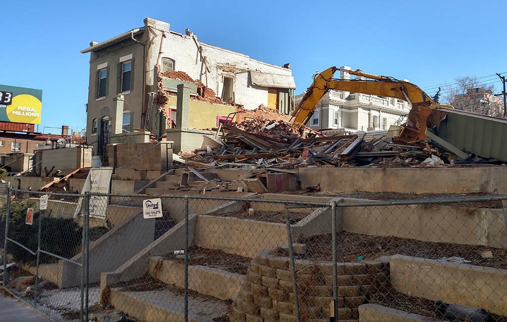 Crews demolish a row of three homes on the 900 block of Lincoln Street. (Burl Rolett)